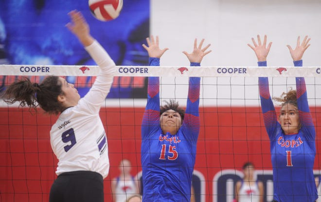 Cooper's Jada Willis (15) and Alexis Garcia (1) try to block a shot by Wylie's Keetyn Davis. Wylie won the District 4-5A match 25-23, 25-22, 26-24 on Tuesday, Oct. 23, 2018, at Cougar Gym.