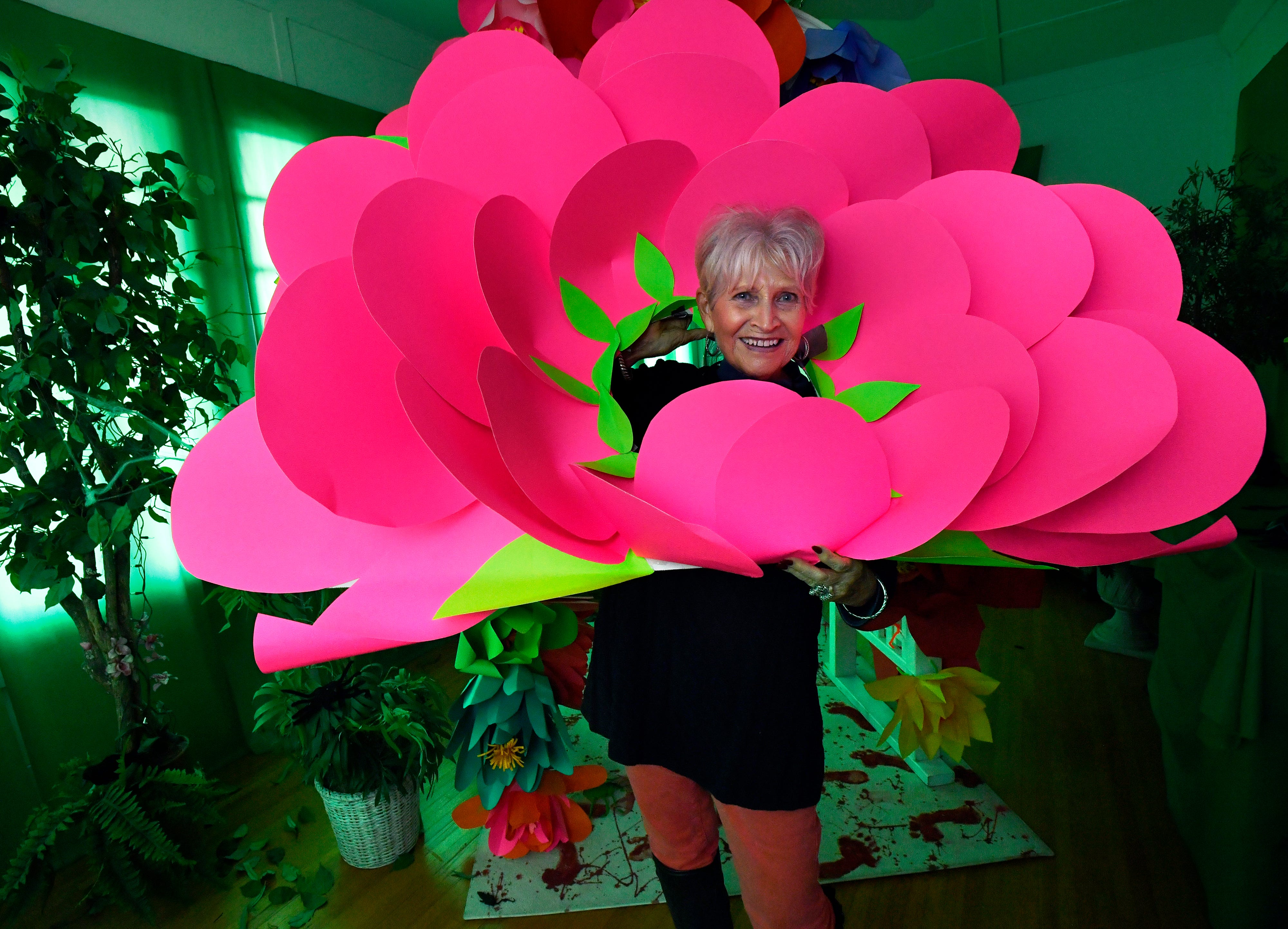 Janet Payne wears a repurposed floral decoration made from construction paper inside the Swenson House.