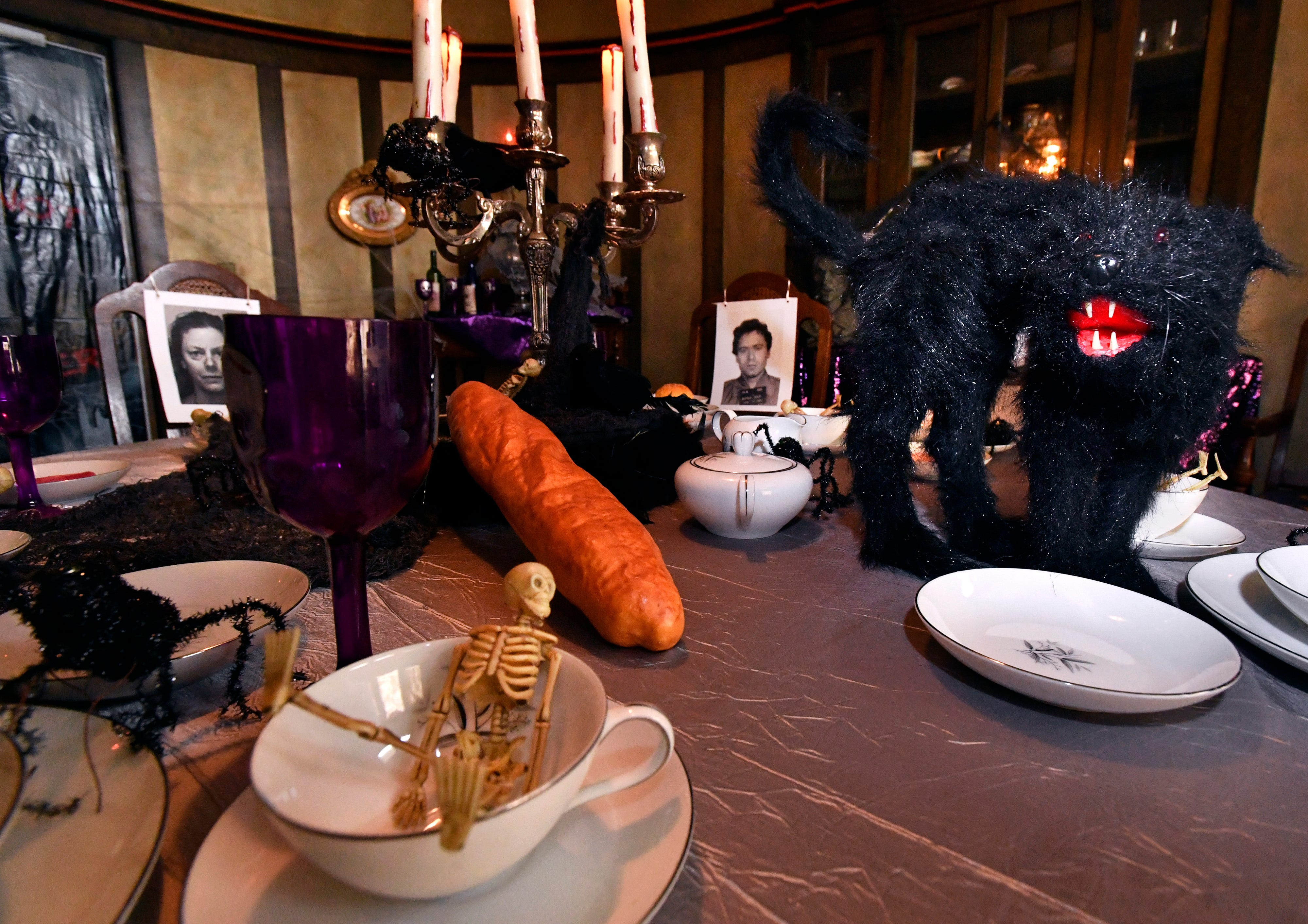 The dining room table is decorated with spooky creatures and the mug shots of serial killers at the Swenson House Wednesday for Halloween.