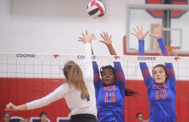 Cooper's Dazz Larkins (12) and Bri Garcia (10) defend at the net as Wylie's Karis Christian hits the ball. Wylie won the District 4-5A match 25-23, 25-22, 26-24 on Tuesday, Oct. 23, 2018, at Cougar Gym.