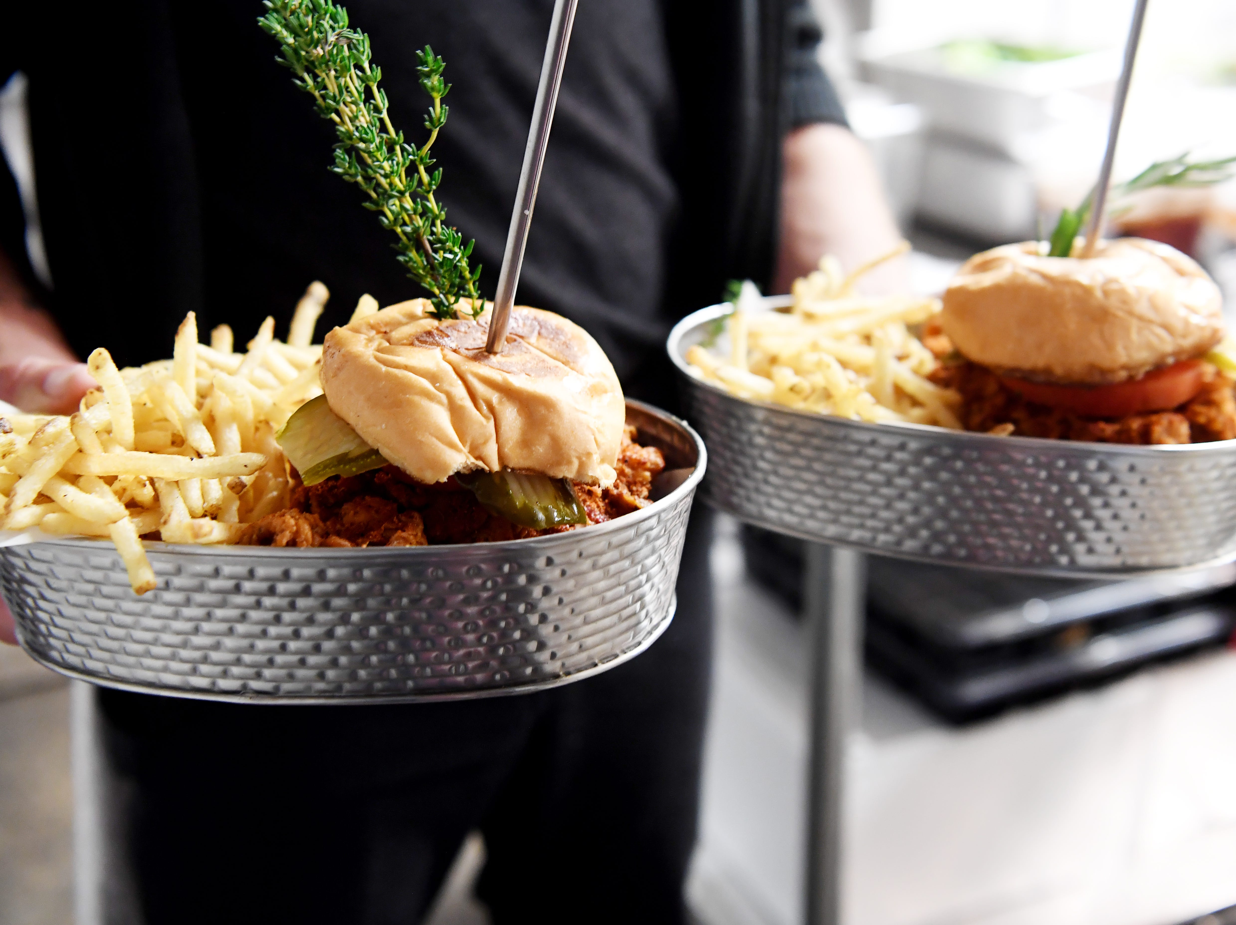 """The Continental Lounge's """"Frog's Famous"""" fried chicken sandwich with fries."""