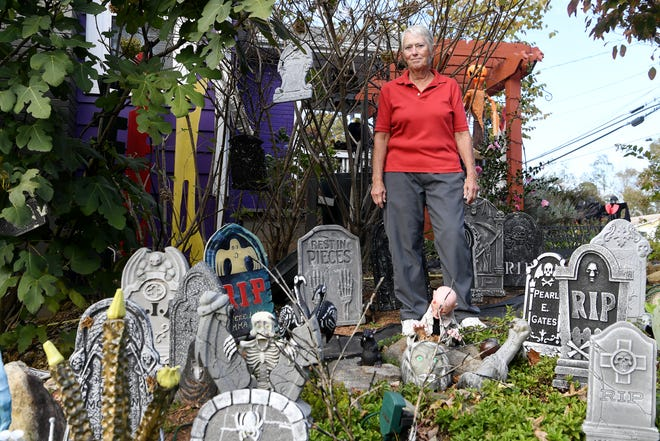 Paula Beatty stands among the Halloween decorations in her yard in West Asheville.