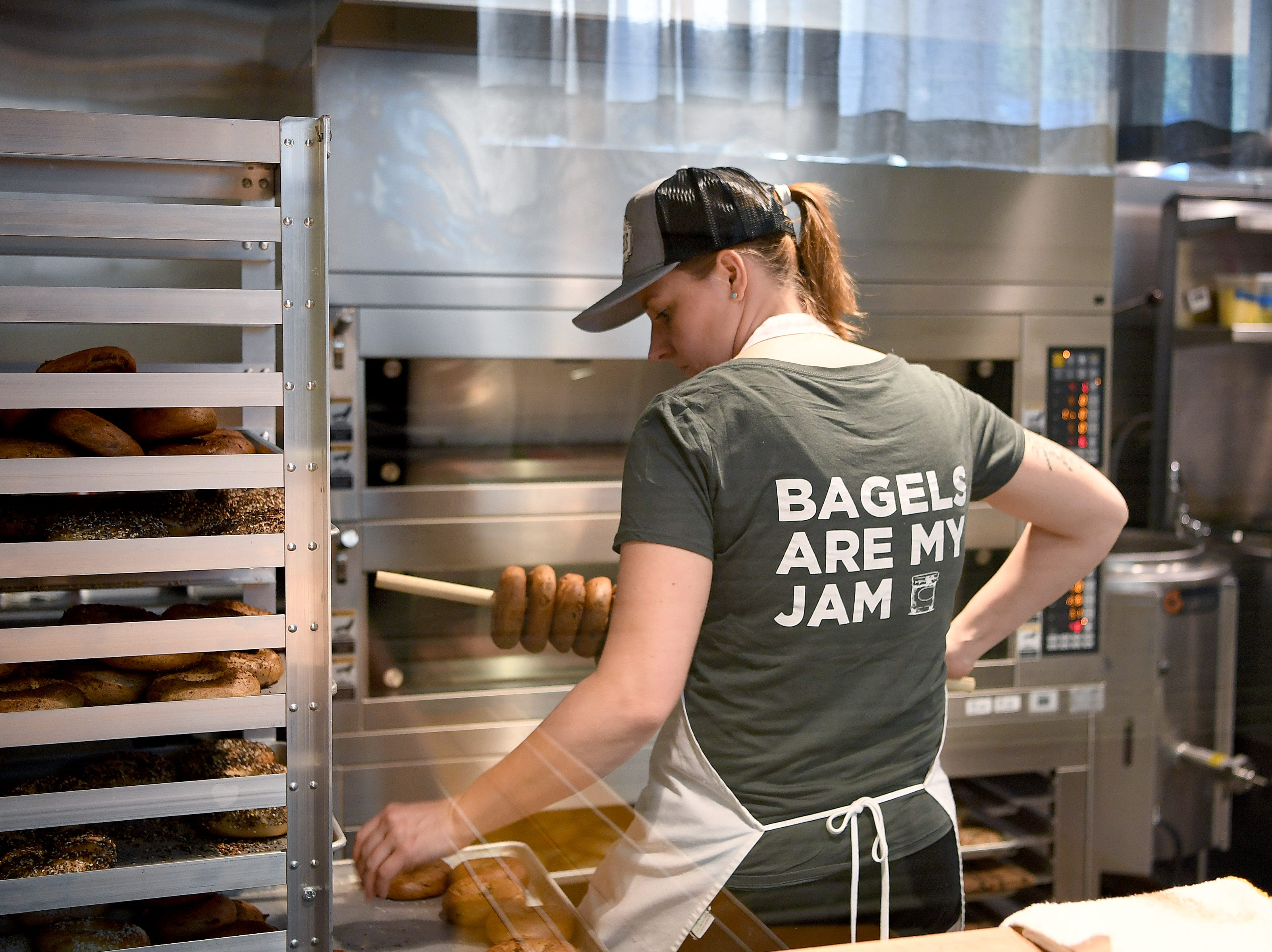 A staff member loads bagels on a peg at the soon-to-open Button & Co. Bagels on Lexington Avenue to prepare for a friends and family preview on Oct. 24, 2018. The restaurant opens to the public on Friday.