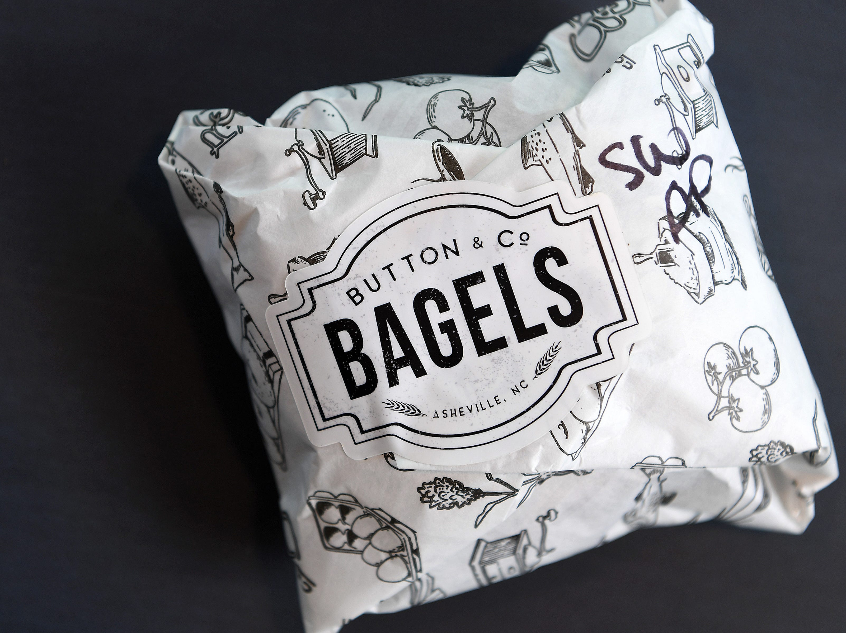 A bagel sandwich is wrapped in special paper with a customized sticker at Button & Co. Bagels on Lexington Avenue during a friends and family preview on Oct. 24, 2018. The restaurant opens to the public on Friday.