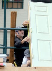 Dave Dimmen, top, and David Day, bottom, measure a door for a storage shed they are building at the Georgia's House women's shelter in Bremerton on Wednesday. Volunteers have been assisting the shelter with renovations.