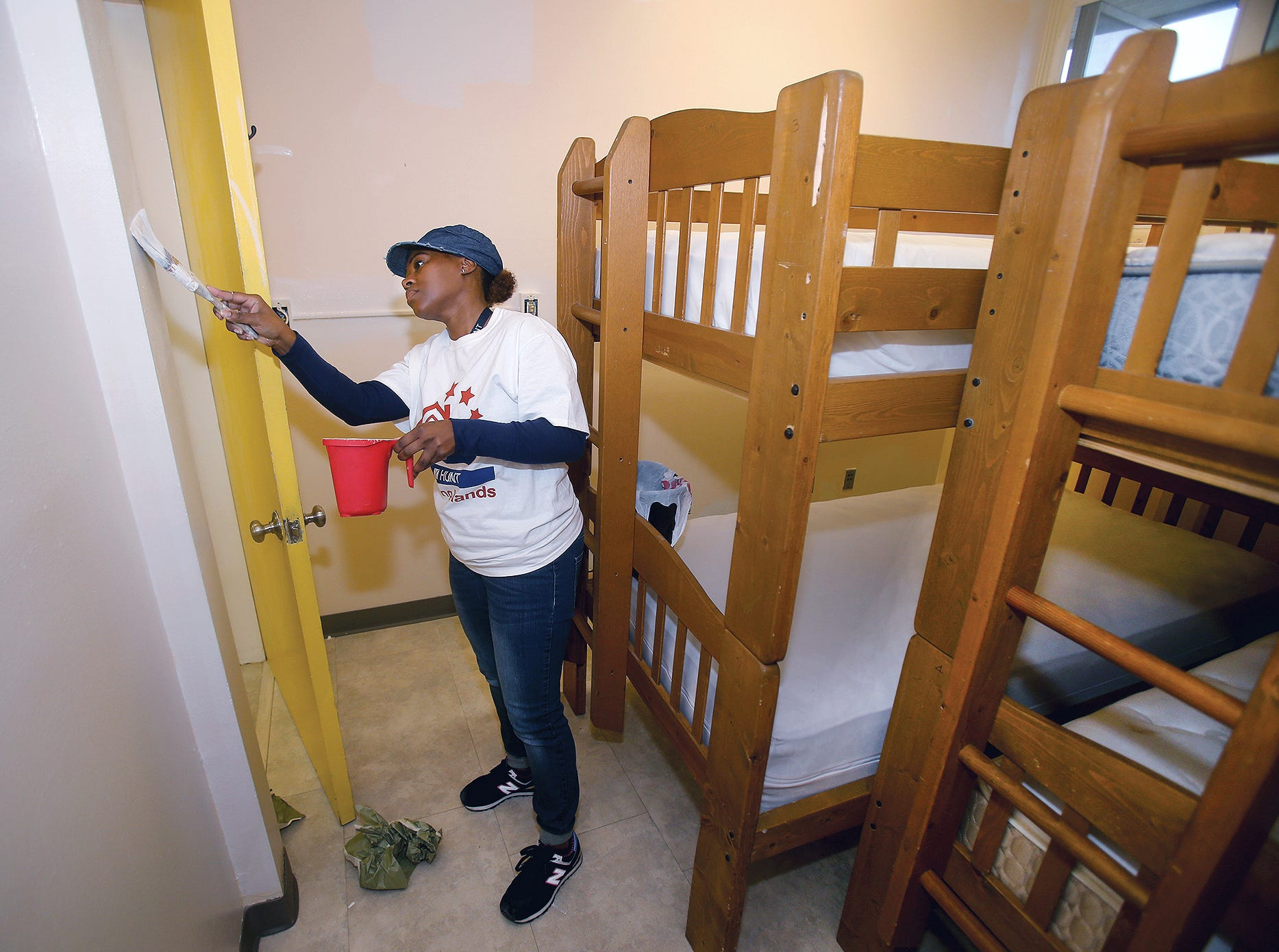 Myseha Mosley paints one the Georgia's House women's shelter rooms on Wednesday, October, 24, 2018.The shelter that helps homeless women and domestic violence victims reclaim stability. The shelter relocated its residents this month due to a bed bug scare and is taking the opportunity to complete renovations. A team ofvolunteers from Hunt Maintenance at Bangor, helped.