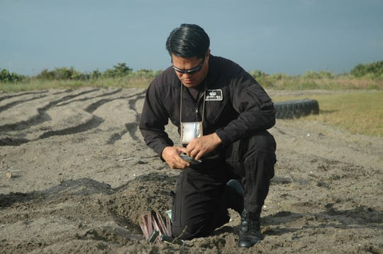 File photo from 2007 of Tech. Sgt. Ferdinand Smith of the Patrick Air Force Base Explosive Ordnance Disposal team preparing the flexible explosives that would be detonated to dispose of the charges buried by his feet.