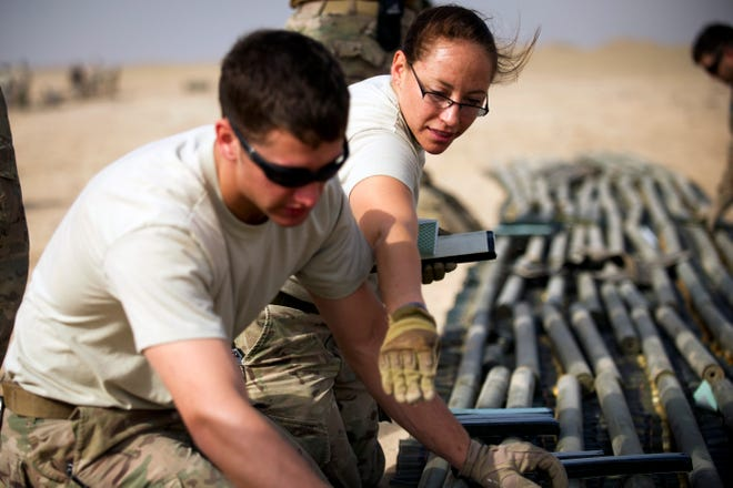 This file photo from 2014 shows Tech. Sgt. Angela Olguin, an explosive ordnance disposal technician, instructing Airman 1st Class Keith Bochert on properly placing explosive charges on munitions slated for disposal at an undisclosed location in Southwest Asia. The two EOD Airmen had been deployed to the 386th Expeditionary Civil Engineer Squadron.