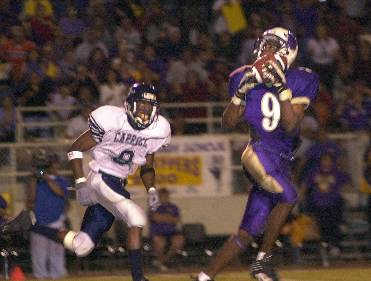 Miller's Darren Lister pulls in a long pass in stride for a touchdown with Carroll's Nathan Johnson trailing Nov. 8, 2001 in Buc Stadium.