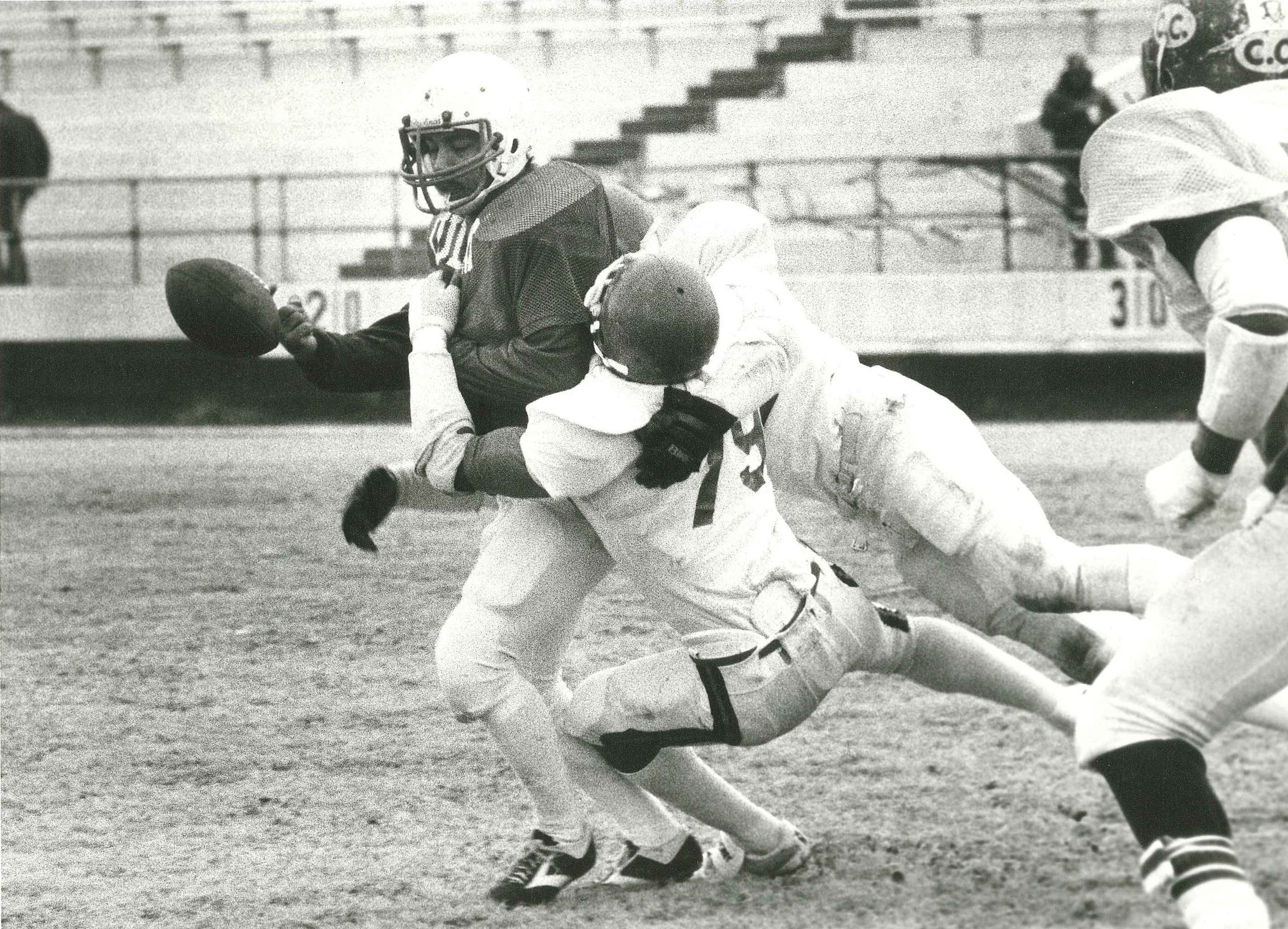 Corpus Christi Army Depot Cobras defenders Herrow Collins (79) and Dan Garcia force LULAC Bronco quarterback Lupe Gutierrez to fumble the ball during the 1984 Menudo Bowl at Buccaneer Stadium.