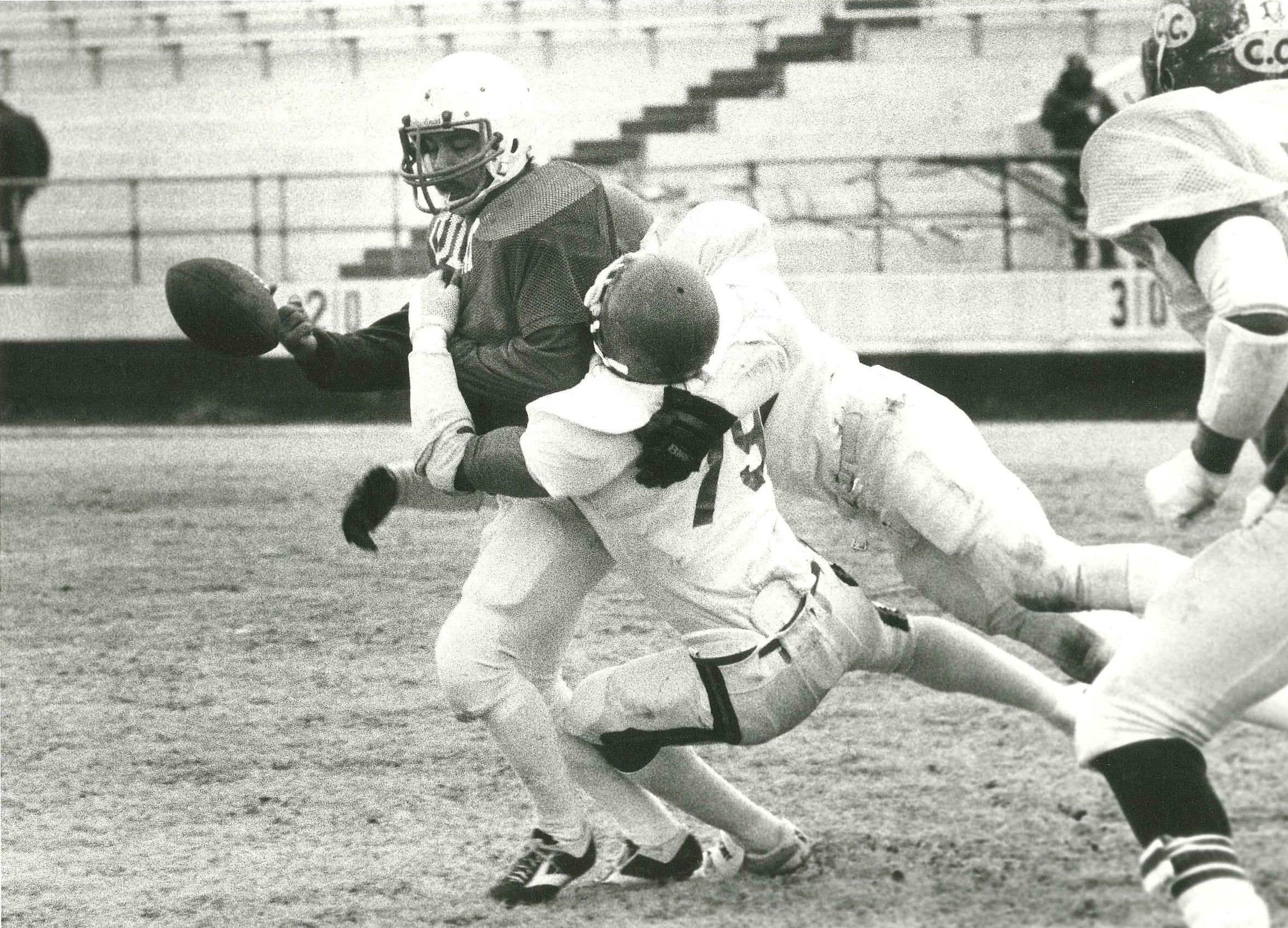 Corpus Christi Army Depot Cobras defenders Herrow Collins (79) and Dan Garcia force LULAC Bronco quarterback Lupe Gutierrez to fumble the ball during the 1984 Menudo Bowl at Buccaneer Stadium.