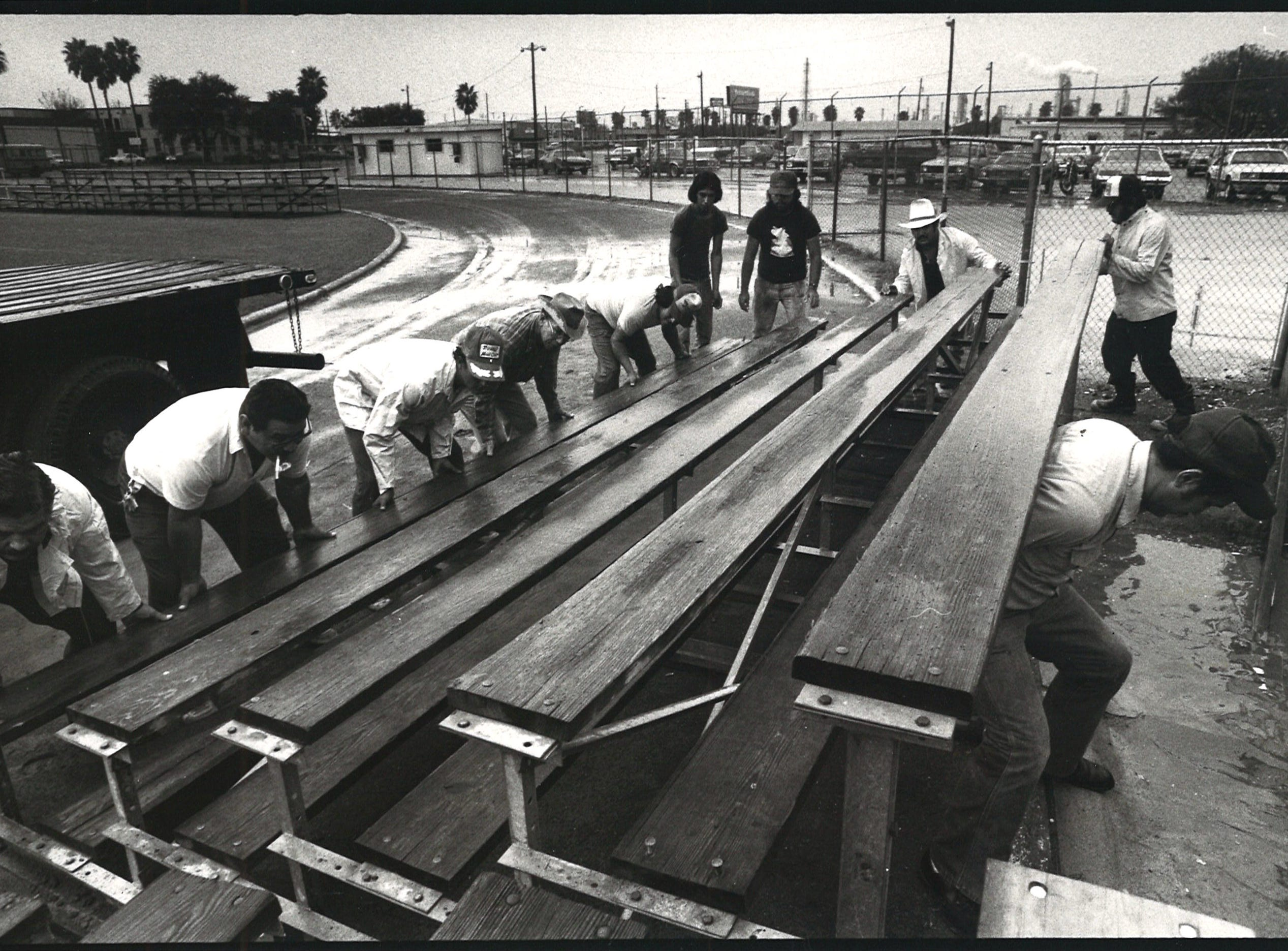 School district employees set up bleachers for the upcoming football games at Buc Stadium as it rains on Nov. 10, 1982.