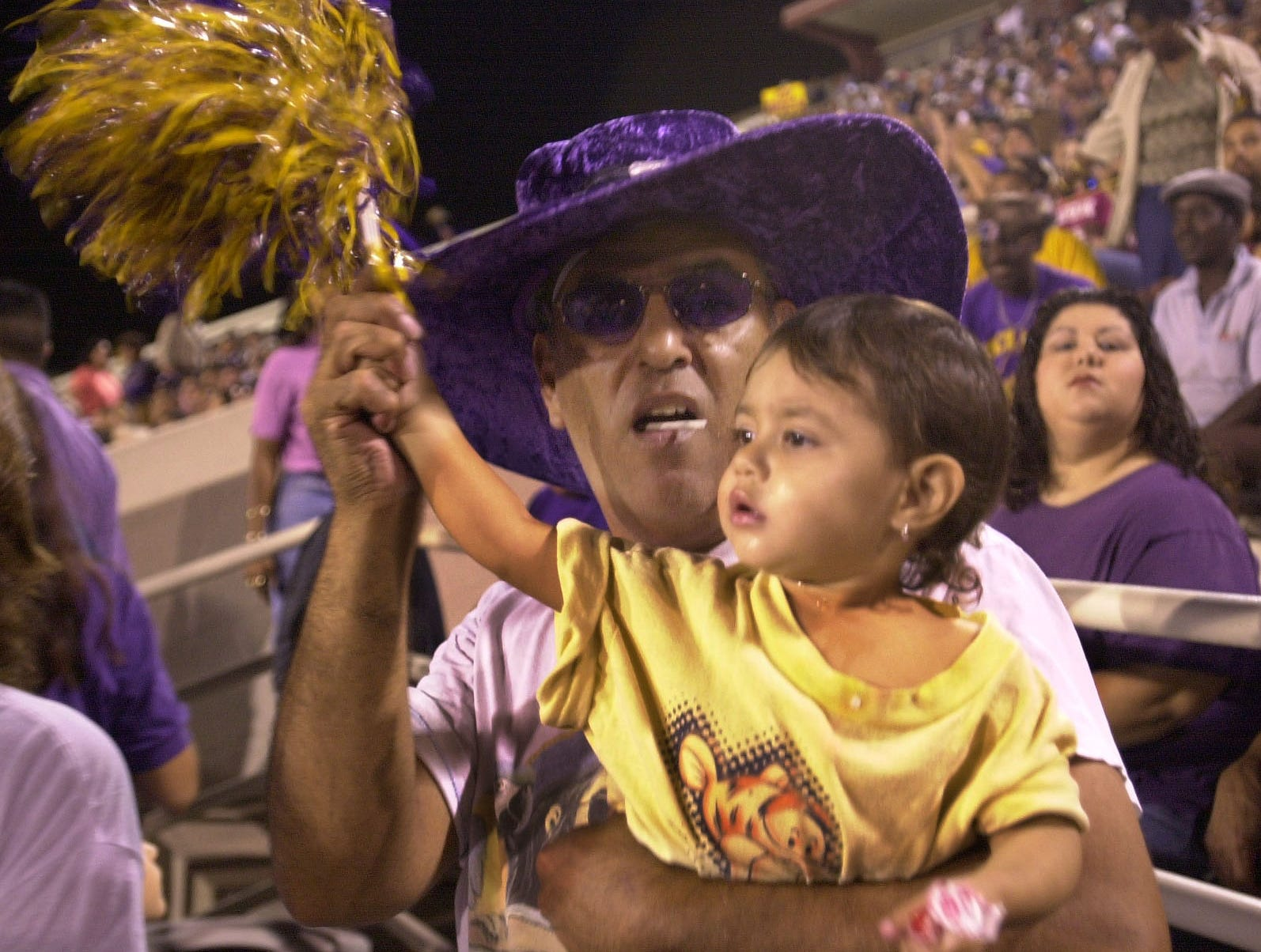 Rey Quijas (left) in a purple velvet hat helps his 20-month old daughter Bellanisa Quijas wave a purple and gold pom-pom on the Miller side of Buc Stadium on Nov. 8, 2001.
