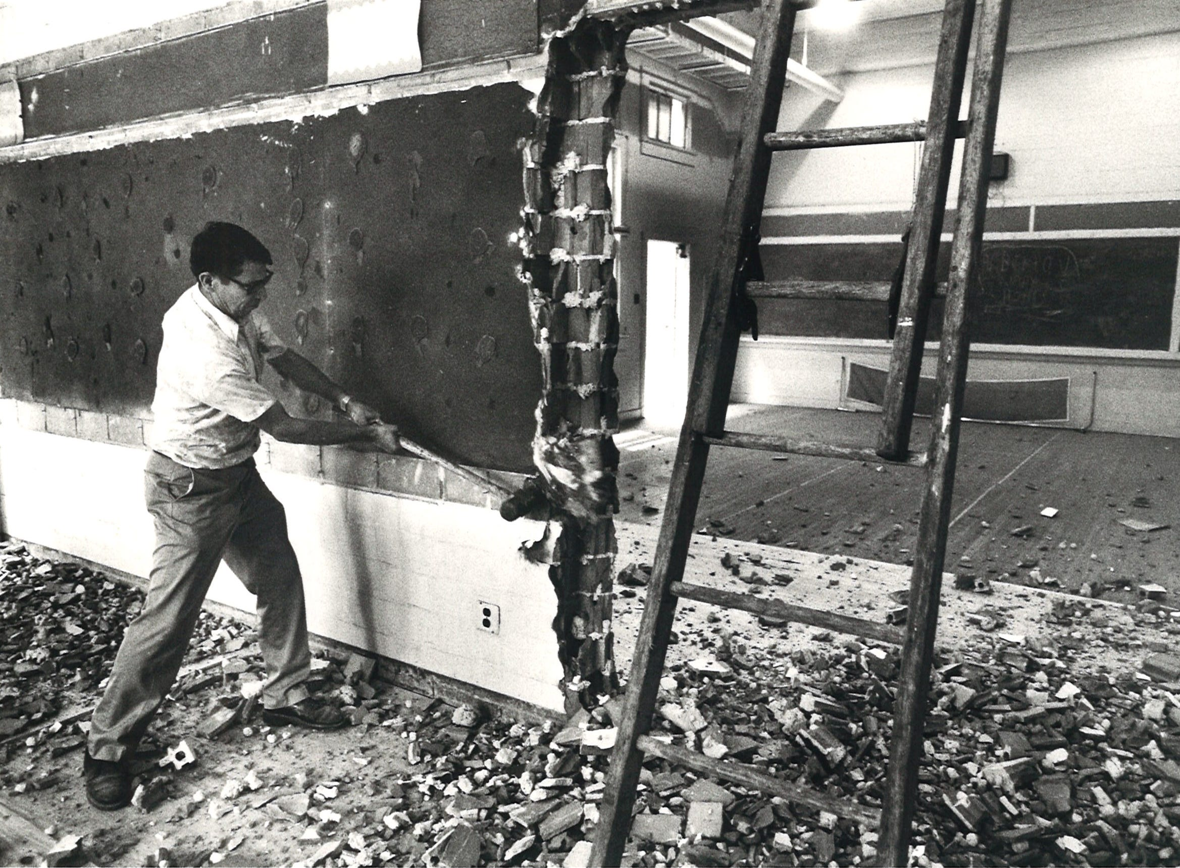 Construction worker Isidro Perez knocks down a wall a Buc Stadium during renovations in August 1982.