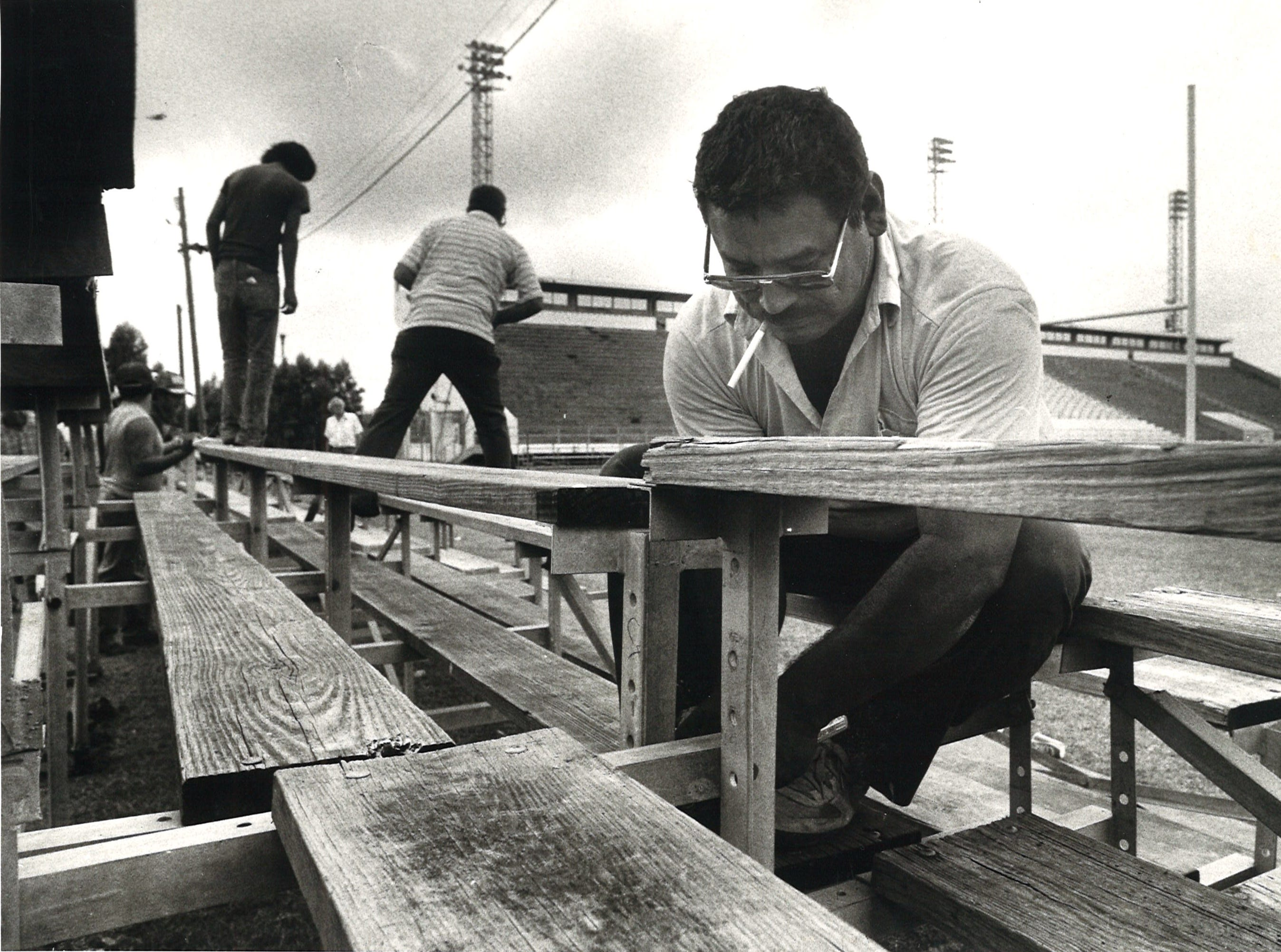 Jesus Ramirez, the caretaker of Buc Stadium, hooks together some of the extra bleachers for the upcoming football games on Nov. 10, 1982.