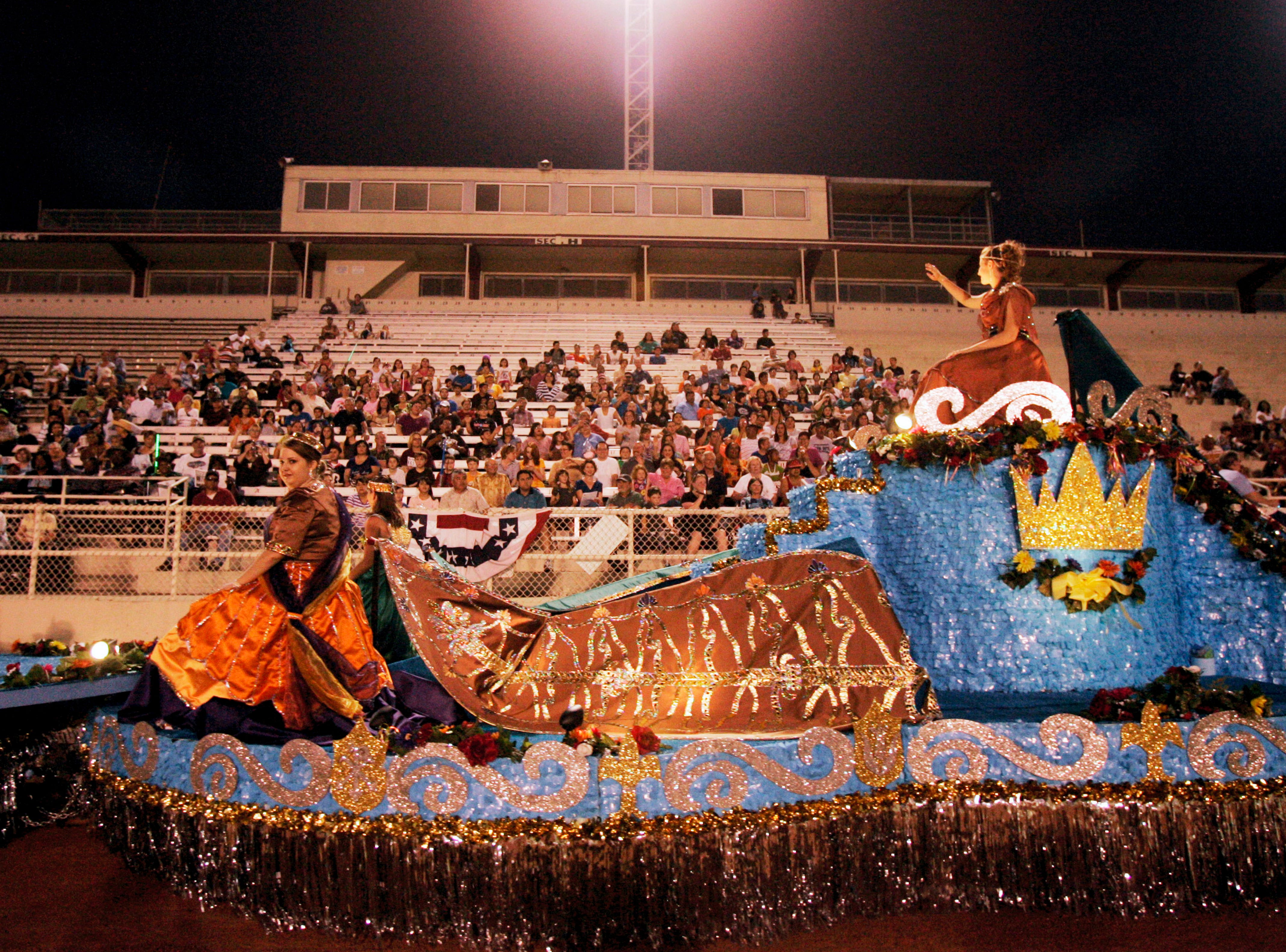Participants on the San Antonio Lutheran Coronation float wave to the crowd Saturday, May 1, 2010 during the Buc Days Illuminated Night Parade at Buc Stadium in Corpus Christi.