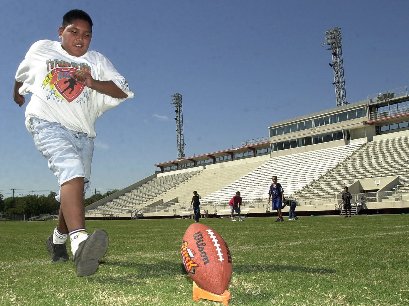 Enrique Pesina, 11, keeps hie eyes on the ball as he lines up for a practice kick during the NFL Punt, Pass and Kick Competition Sept. 29, 2001 at Buc Stadium.
