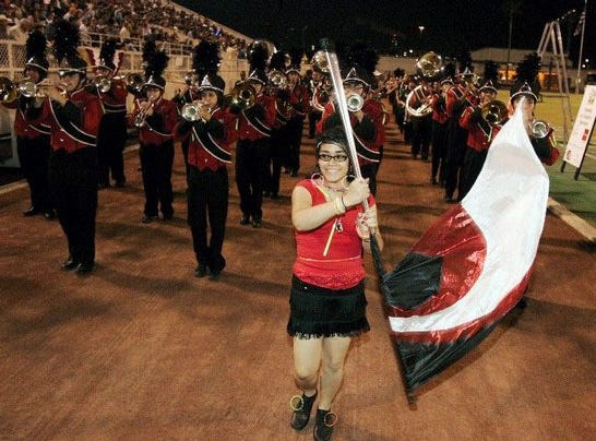 Band and color guard members from West Oso march around the track during the 2010 Buc Days Illuminated Night Parade at Buc Stadium in Corpus Christi.