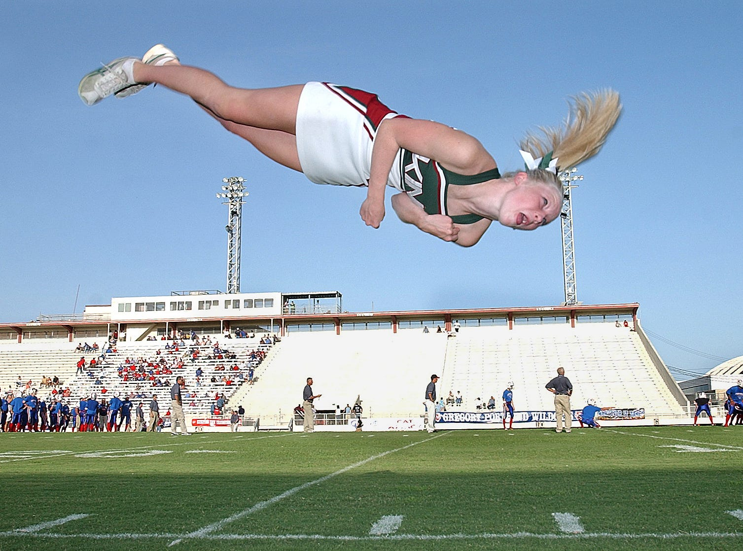 King High School cheerleader Morgan McKay (16) added a twist to her handspring as the King cheerleaders warmed up before the game between King and Gregory-Portland at Buc Stadium on Aug. 26, 2004.