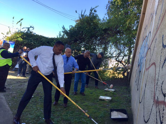 Minister Wasim Muhammad (left to right), Camden Mayor Frank Moran, Councilman Brian Coleman and artist William Butler take paint rollers to a graffiti-tagged PATCO Hi-Speedline overpass.