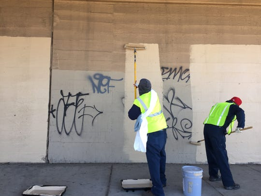 Camden Public Works employees cover graffiti on a PATCO Hi-Speedline overpass in the city's Gateway section.