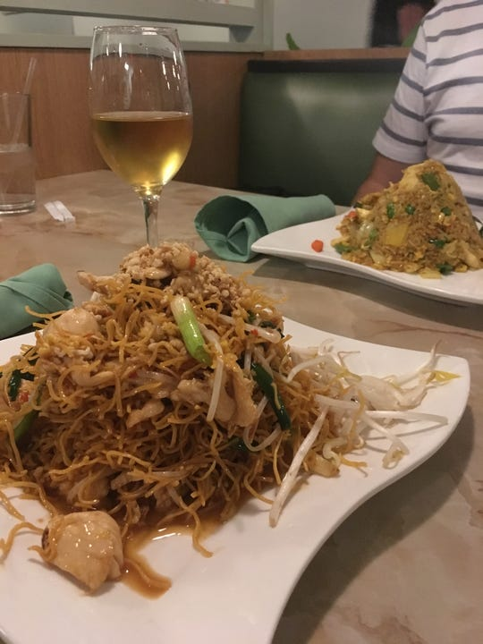 Crispy Pad Thai and plum wine, left, and Pineapple Fried Rice at Green Papaya in Mariemont.