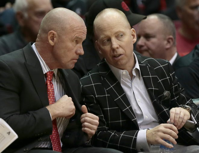 Cincinnati Bearcats head coach Mick Cronin (right) and then-associate head coach Larry Davis talk from the bench during a game at UC on Nov. 24, 2015.