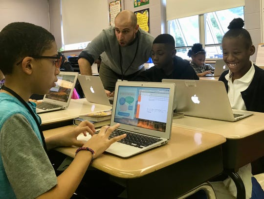Elementary technology teacher Mitch Gorbunoff working with School No. 4 fifth-graders Ryan Irving, Akhenaton DeRose and Ke'Asia Williams on an online discussion.