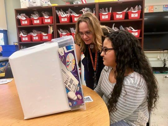 Elementary technology teacher Kim Marie Kefalas helping fourth-grader Tatiana Rivera create a video using a miniature sound studio Kefalas created out of a plastic bin and acoustic foam.