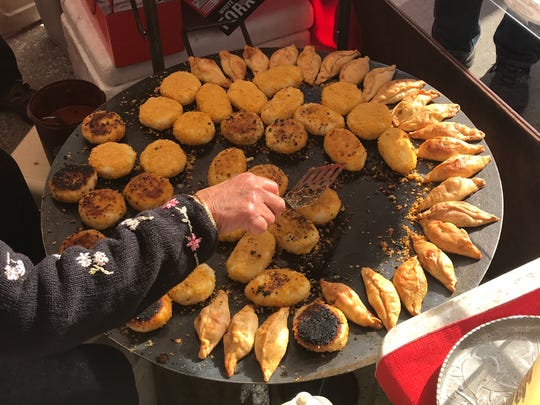 Saloo Sadiq of Clive flips potato patties called 'cutlets' at her stand called Saloo India at the Downtown Farmers' Market in Des Moines.