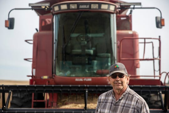 Randy Souder, who farms corn and soybeans, stands in front of his combine on Wednesday, Oct. 24, 2018, in his bean field outside of Rockwell City.