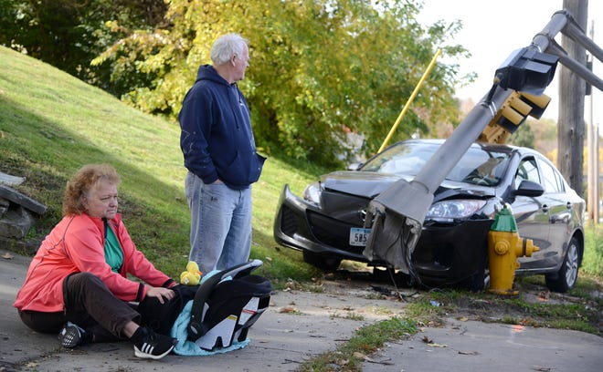 Maria Calhoun, of Clive, sits with a baby found at the scene of a crash involving a stolen car Wednesday, Oct. 24, 2018, at University Ave and Merle Hay Road in Windsor Heights.