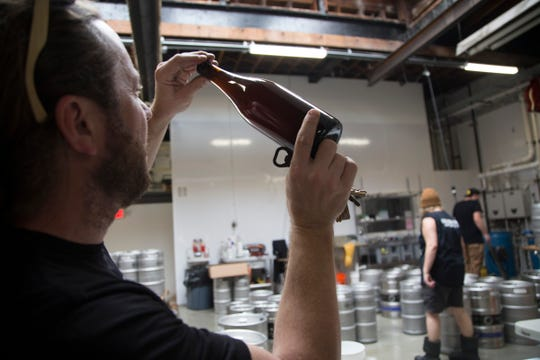 Batch Brewing Co. is working on a new location in midtown Detroit. Batch co founder Stephen Roginson checks a bottle of ÒUp For The Down StrokeÓ a coffee sour beer Wednesday, Oct. 10, 2018.