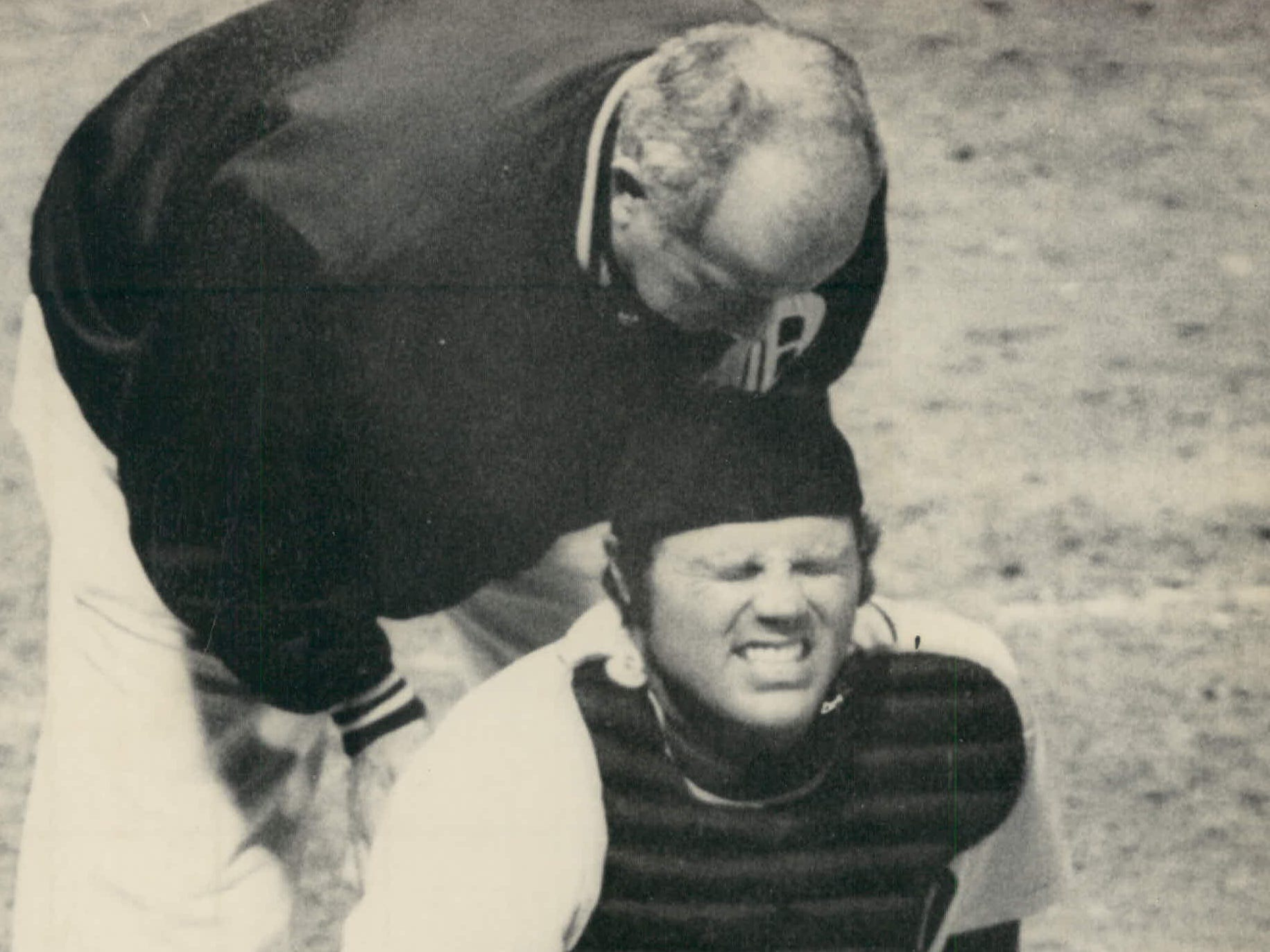 Tigers catcher Bill Freehan grimaces in pain while trainer Bill Behm attempts to help after Freehan was struck in the groin by a ball pitched by Vern Ruhle in the fifth inning of Milwaukee Brewers game at Tiger Stadium on May 8, 1975.