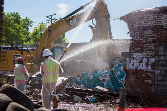 Gayanga Co. laborers Eric Cox, left, and Richard Allen both residents of Detroit, wet down a commercial demolition on DetroitÕs west side Monday July 9, 2018.Detroit's Land Bank demolition program seriously lacks diversity. Just 16 percent of the hundreds of millions in federal dollars awarded since 2014 have gone toward black owned companies. Gayanga Co. has received more than $4 million in contracts and nearly 90 percent of its staff are Detroit residents. We follow them on a commercial demolition on Detroit's west side.