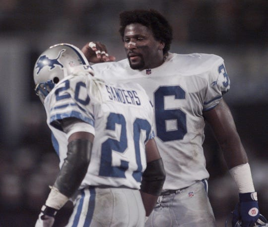 Lions safety Bennie Blades congratulates running back Barry Sanders during a game against the Chargers on Nov. 11, 1996, in San Diego.