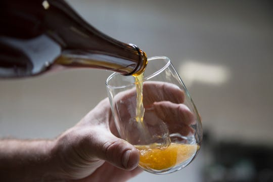 Batch Brewing Co. is working on a new location in midtown Detroit. Batch co founder Stephen Roginson pours a bottle of ÒUp For The Down StrokeÓ a coffee sour beer Wednesday, Oct. 10, 2018.