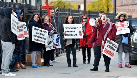 Ashourina Slewo, second from right, of Madison Heights, yells into her bull horn as she leads protesters in front of Detroit's federal courthouse Wednesday morning. Her Iraqi-born father, Warda Slewo, was recently released on bond after being detained for nine months.