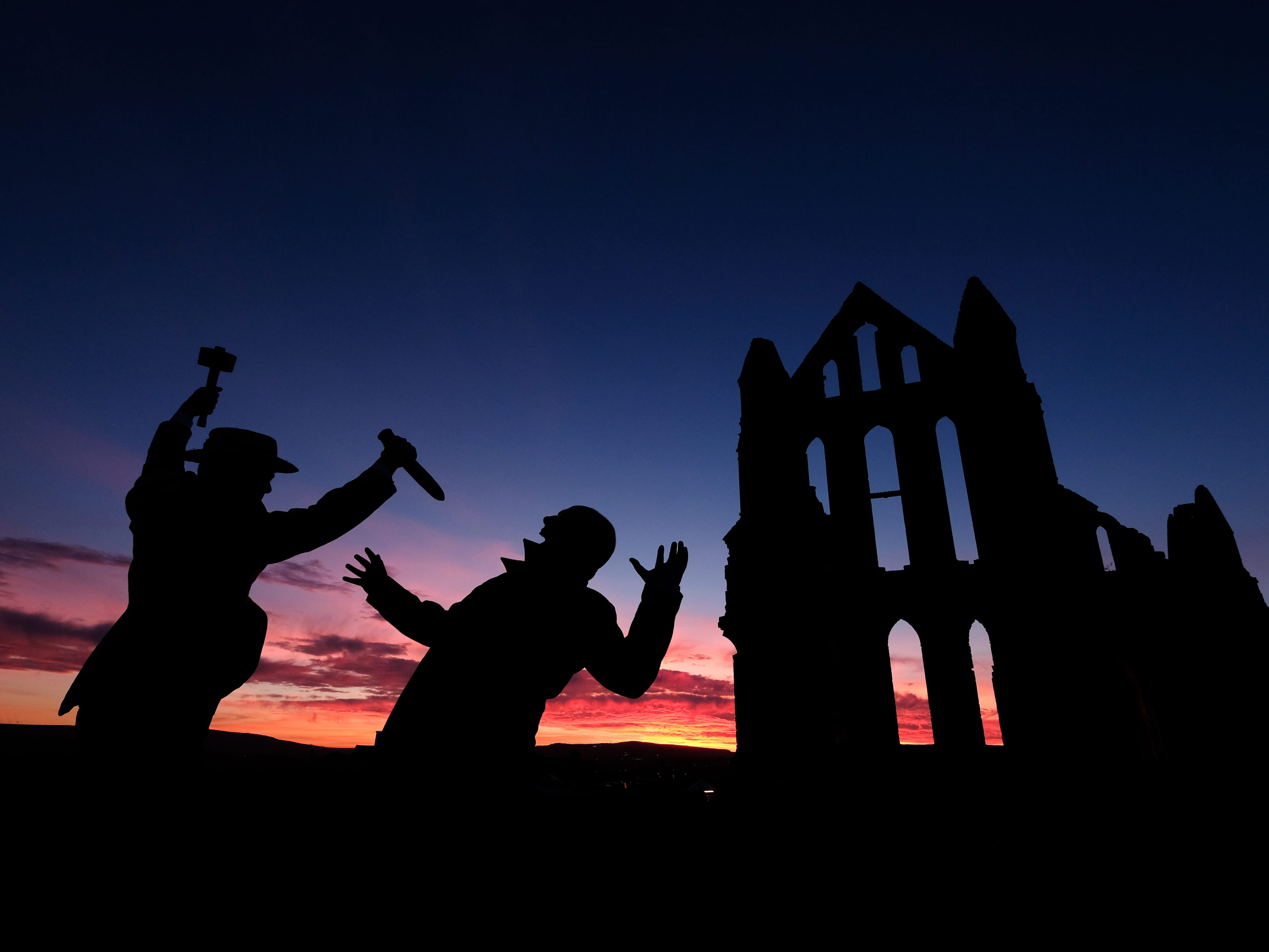 Actors Craig Cowdroy (L) and Richard Hollick pose for pictures during a press evening ahead of a light display illuminating the historic Whitby Abbey on October 24, 2018 in Whitby, England. The abbey will be illuminated over Halloween Week and visitors will be able to experience the site after dark and wander through the dramatic ruins of the abbey famously noted for being the inspiration behind Bram Stokers Dracula. The famous Benedictine abbey sits on East cliff in the Yorkshire seaside town in a commanding position overlooking the North Sea.