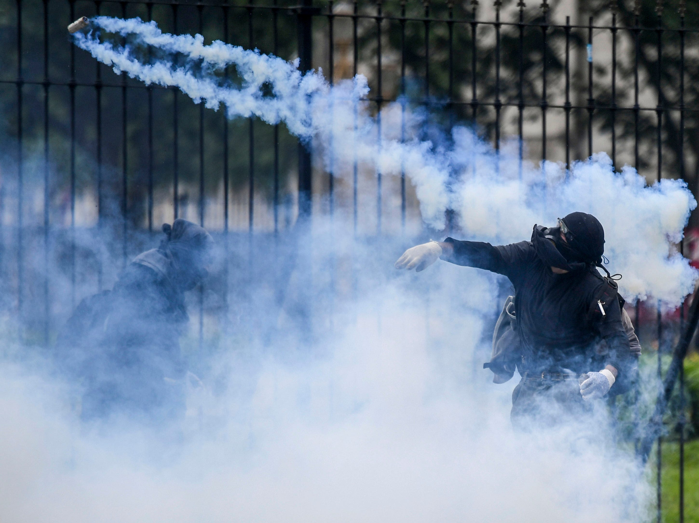 A demonstrator throws a tear gas canister back at riot police outside the Congress while Argentine Deputies began the discussion on the governments austere 2019 budget, in Buenos Aires on October 24, 2018. - Argentinian Deputies Chamber carries out the first debate of the 2019 budget, with the purpose of achieving the fiscal balance agreed with the International Monetary Fund (IMF), but rejected by unions and social movements that called protest demonstrations.