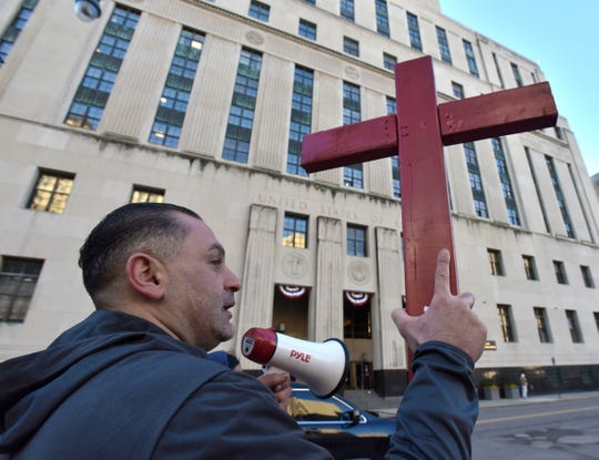 Simon Owshana of Detroit, holds up a red cross as he and others protest in front of the federal courthouse Wednesday.  Owshana was released on a personal bond after being detained for 14 months for possessing 20 grams of marijuana. He has  lived in the U.S. for 20 years and has a court hearing on November 29.