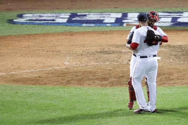 Craig Kimbrel is congratulated by his teammate Sandy Leon of the Boston Red Sox after closing out the game.