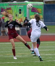 Lauren Beall (16) of Corning boots the ball ahead in front of Elmira's Michaela Trivisonno during a Section 4 Class AA girls soccer semifinal Oct. 24, 2018 at Ernie Davis Academy.