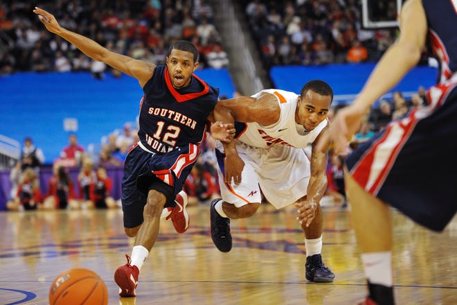 Southern Indiana's Lawrence Thomas (12) and  Evansville's Troy Taylor (5) go for a loose ball after Taylor lost control of the ball in the first half of their exhibition game at the Ford Center, Saturday night, Oct. 27, 2012.