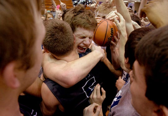 Reitz's Alex Stein (center) and Elijah Dunham (5) celebrate after beating Richmond in their semi-state game at Seymour High School Saturday afternoon, March 21, 2015.