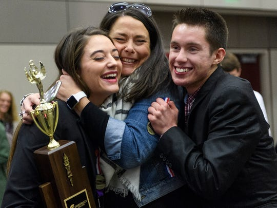 Amy Davis, center, embraces her daughter Jalyn Davis, left, and teammate Jamie Borne, right, after it was announced that they won first place in the University of Evansville's fourth annual High School Changemaker Challenge, Wednesday afternoon, Oct. 24, 2018. The North High School students including teammate Ashlyn Thompson, not pictured, were awarded four-year full tuition scholarships to the University of Evansville.