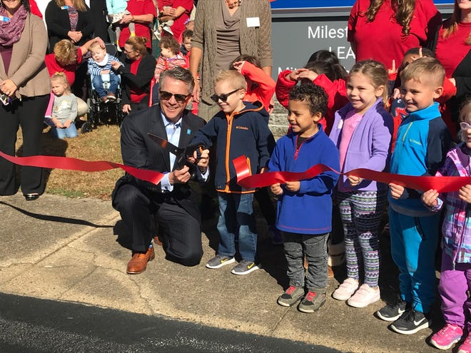 Evansville Mayor Lloyd Winnecke gets a pint-sized assist at Wednesday's ribbon-cutting ceremony for the Easterseals Early Learning Center.