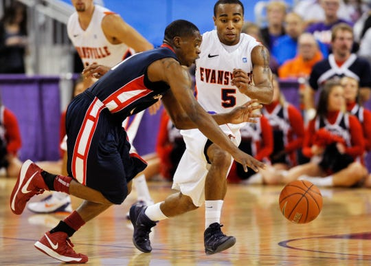 Southern Indiana's Kenyon Smith (1) drives the ball down the court as Evansville's Troy Taylor (5) defends in the first half of their exhibition game at the Ford Center, Saturday night, Oct. 27, 2012.