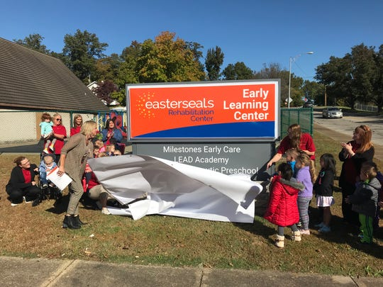 Easterseals President Kelly Schneider, along with a host of caregivers and young students, unveil the new sign rebranding Easterseals' facility on Cullen Avenue as the Early Learning Center.