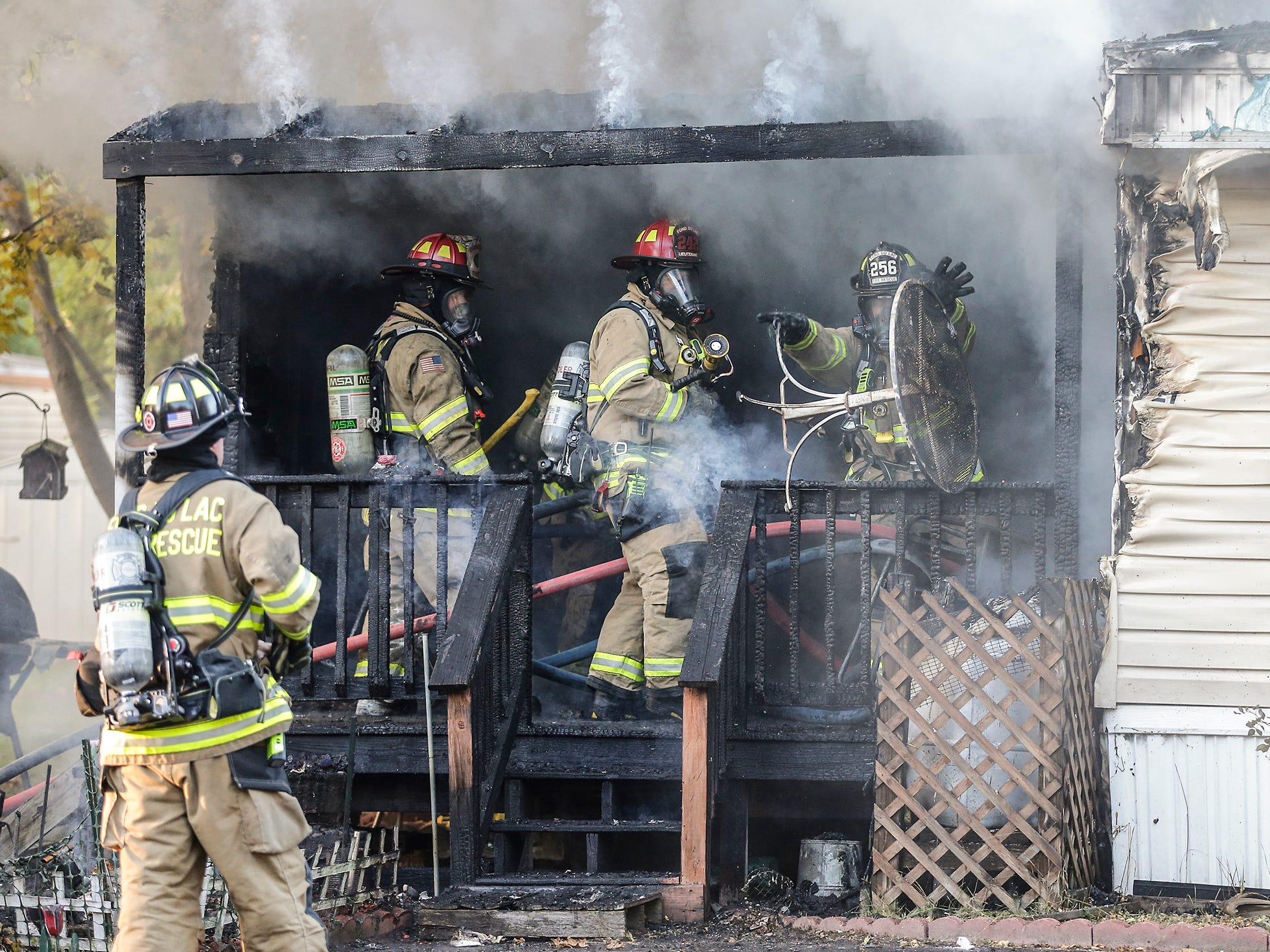 A fire fighter throws a piece of furnature out of a mobile home that was on fire Tuesday, October 23, 2018 at 21 Gaslight Drive in the Gaslight Terrace mobile home park in North Fond du Lac, Wisconsin. Multiple fire departments were on hand to fight the blaze. Doug Raflik/USA TODAY NETWORK-Wisconsin